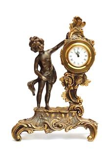 白で隔離される女性の置物とアンティークの時計