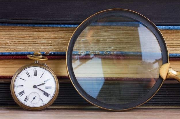 Старинные часы с лупой на фоне старинных книг
