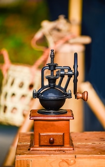 Antique coffee grinder placed on a wooden table