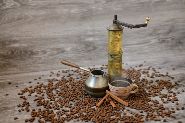 Antique coffee grinder with cup, coffee maker and beans