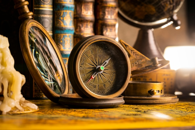 Antique compass on the background of the globe and books. vintage style. 1565 old map of the year.
