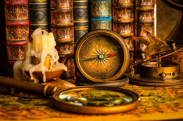 Antique compass on the background of the magnifying and books. vintage style. 1565 old map of the year.