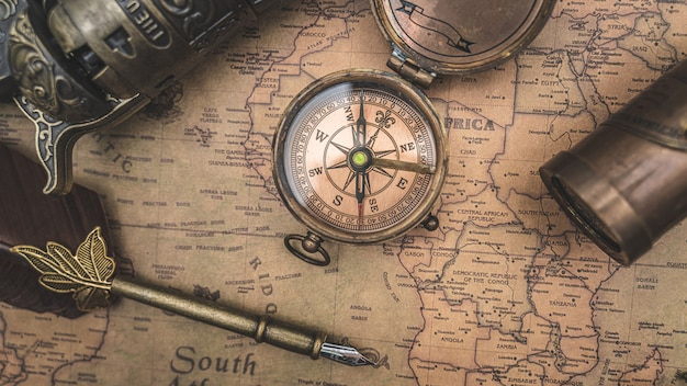 Antique compass and quill pen on old world map