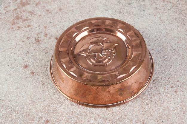 Античная медная форма для торта на бетонном столе.
