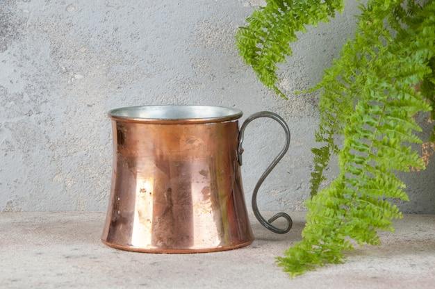 Античная медная кружка и зеленое растение на бетонном столе.