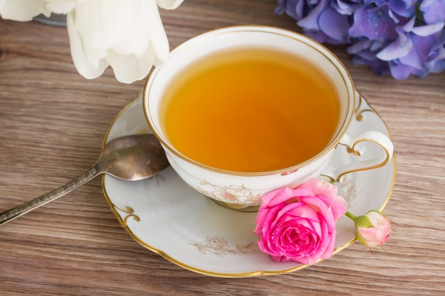 Antique cup of tea with mix of flowers