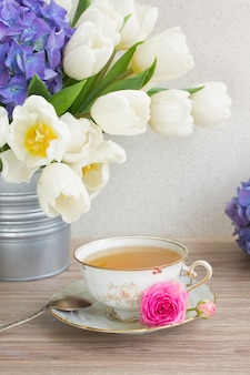 Antique cup of tea with white tulips