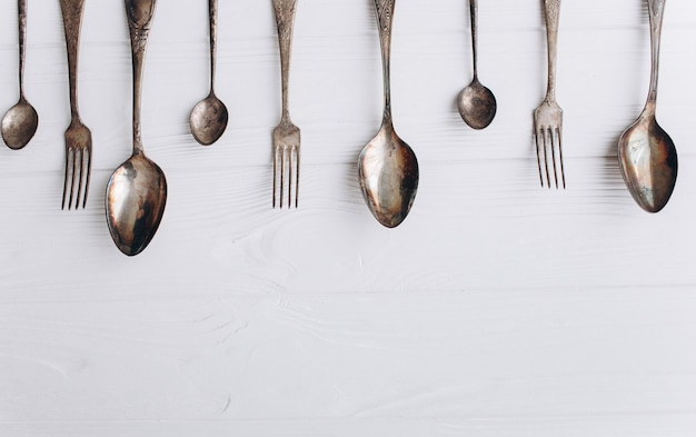 Antique cutlery.old silver spoons and forks on  wooden background