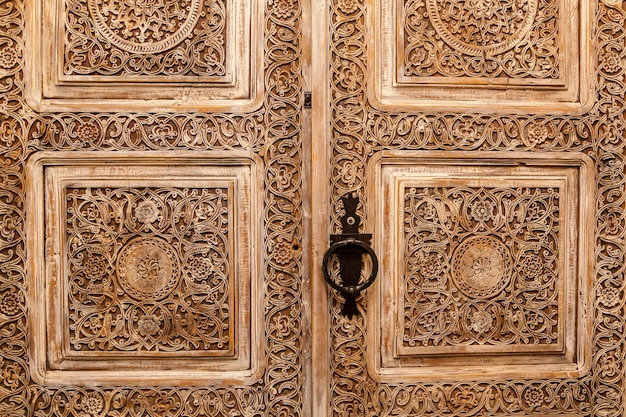 アンティークのドア。彫刻が施されたヴィンテージのスタイリッシュな木製のドア、大きなハンドルが付いた茶色。