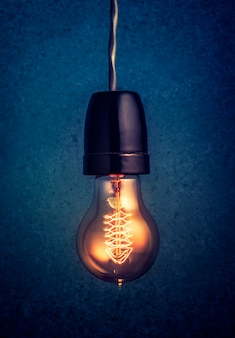 Antique edison style filament light bulbs hanging light bulb over dark background.