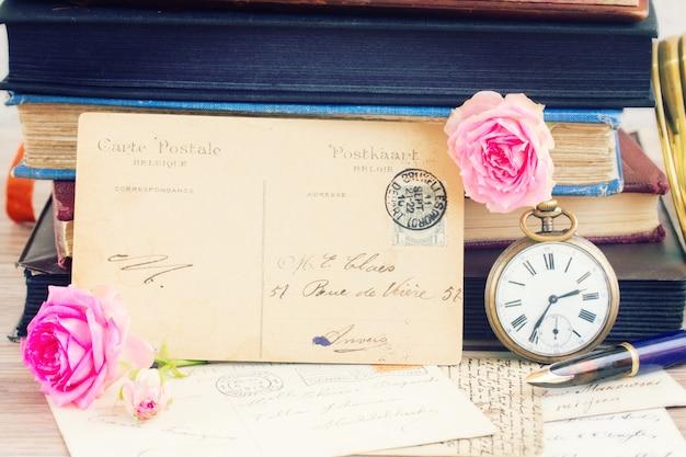 테이블에 꽃과 책이 있는 골동품 빈 엽서