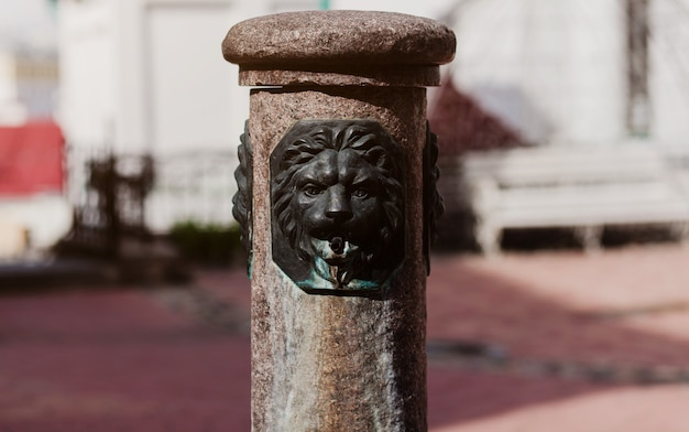 Antique european fountain with a lion's head on one of the streets. classic european fountain