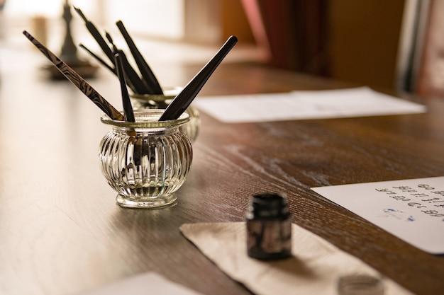 나무 탁자에 있는 골동품 깃털 펜, 오래된 편지, 빈티지 엽서, 잉크. 레트로 향수 감상적인 배경입니다. 쓰기 종이 뒤에 나무 테이블에 쓰기 날개.