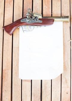 木製の床に白紙のアンティーク銃器。