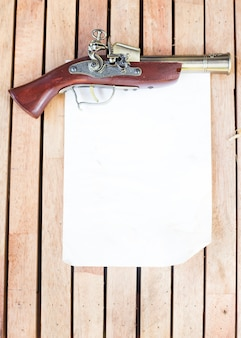 Antique firearms with blank paper on the wooden floor.