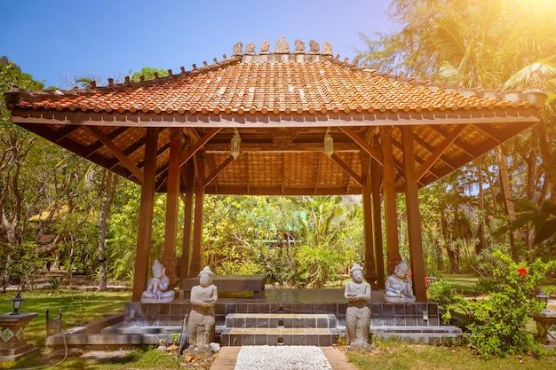 Antique gazebo pavilion roof asian style pagoda summer sunny tropical gardenstone path statues