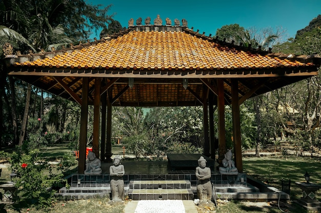 Antique gazebo pavilion with a roof asian style pagoda. in a summer tropical garden. a stone path along which the statues stand leads to the building. inside the area of rest and meditation.