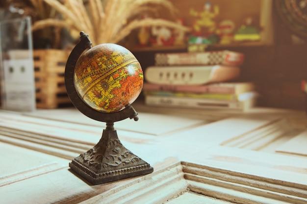 Antique globe model on wood table with orange sunlight, vintage style.