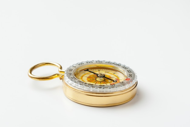 Antique golden compass on white background