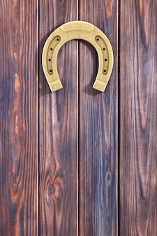 Подкова античного золота утюга ржавая вися на крупном плане крайней деревянной двери доски. 3d рендеринг