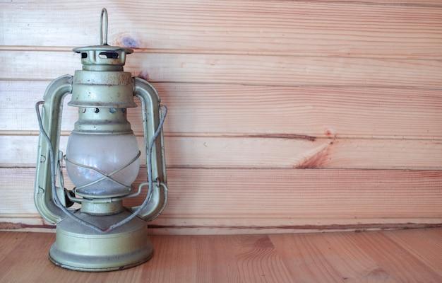アンティーク灯油ランプスタンド。テキストのためのスペース。素朴な木製の背景。本格的なキャンプランプ。季節の旅