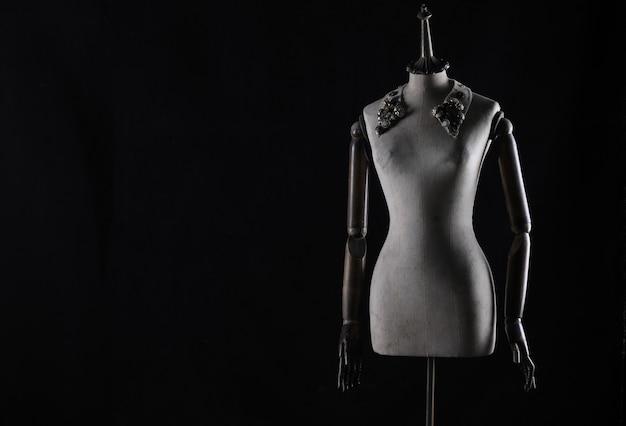 검은 배경에 고립 된 골동품 마네킹