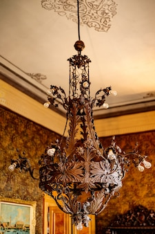 Antique massive metal chandelier with bulbs in the castle