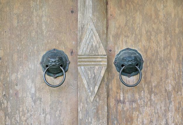 An antique metal knocker on a wooden door