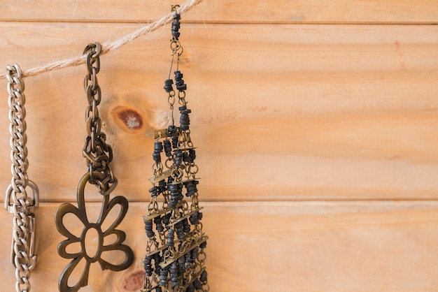 Antique metallic and beads bracelet hanging on jute string against wooden wall
