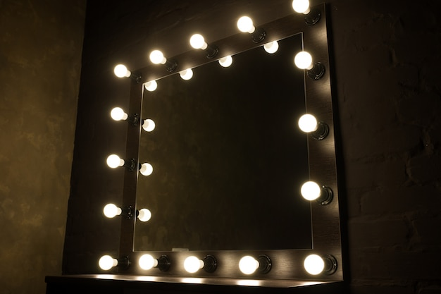 Старинное зеркало с лампами на черном фоне