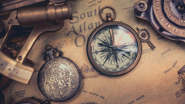 Antique nautical compass on map