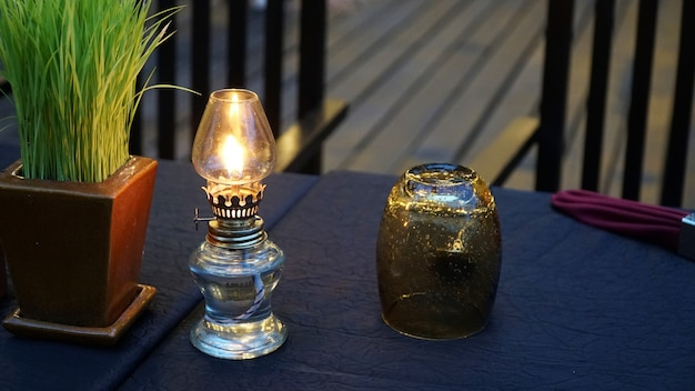 Antique oil lamp and glass on the table