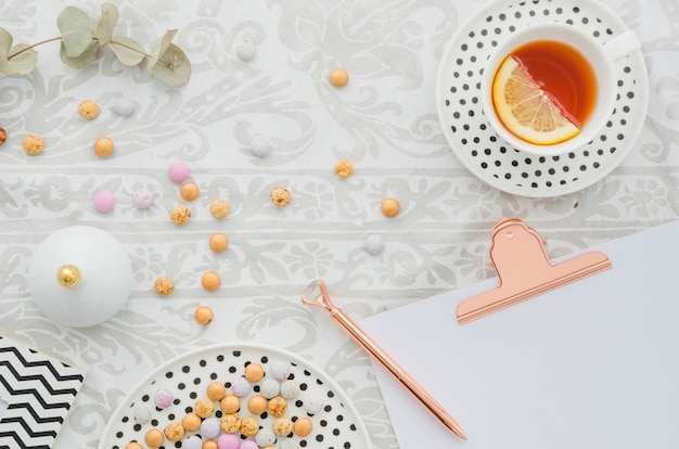 Antique pen on clipboard with candies and ginger lemon tea cup on tablecloth