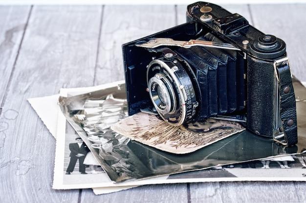 木製のテーブルに古い写真の山とアンティークフォトカメラ