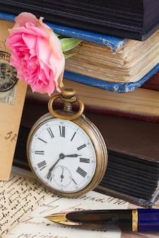 골동품 회중 시계는 빈티지 책과 문자 배경에 가깝습니다.