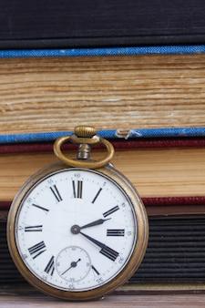 Старинные карманные часы крупным планом на фоне старинных книг