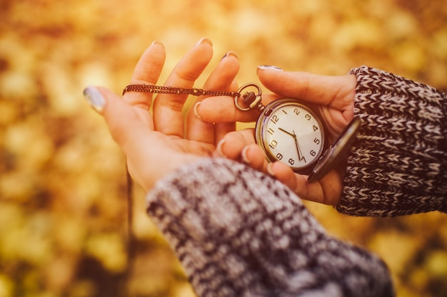Antique pocket clock in hands on an autumn background close-up on the street