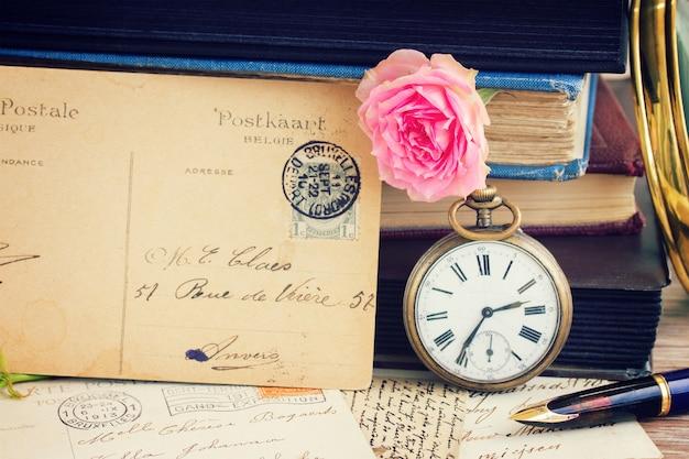 빈티지 책과 편지 배경에 엽서가 있는 골동품 회중 시계