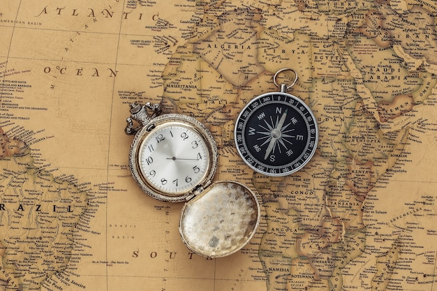 Antique pocket watch and compass on old map. travel, adventure concept