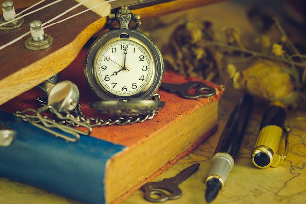 An antique pocket watch leaned against a ukulele and old book with vintage map