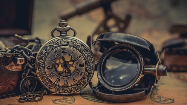 Antique pocket watch and magnifying glass