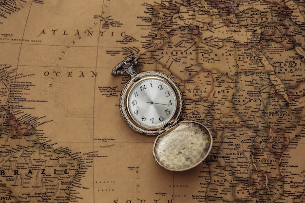Antique pocket watch on an old map