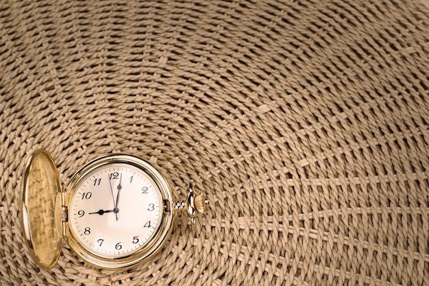 Старинные карманные часы на фактурной тканой соломке. крупный план.