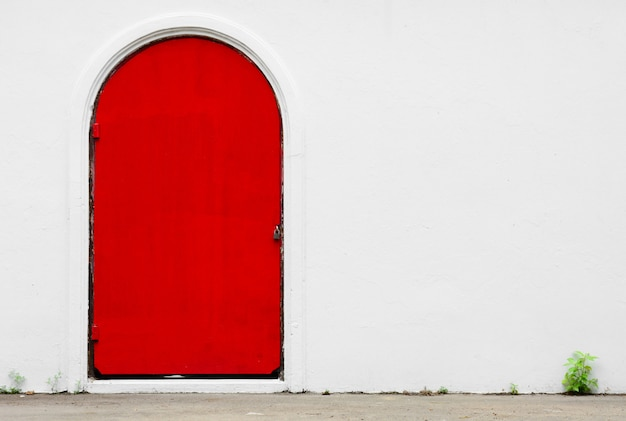 Antique red door at a white concrete wall