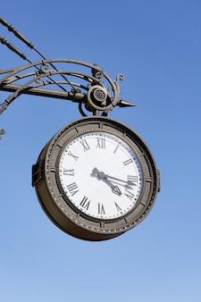 На улице города висят старинные круглые часы с римскими цифрами.