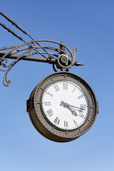 Antique round clock with roman numerals hang on the street of the city. close up