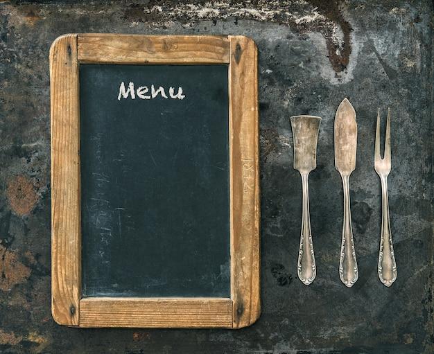 サンプルテキストメニュー付きのアンティークシルバーカトラリーと黒板。ヴィンテージスタイルのトーンの写真。食品のコンセプト