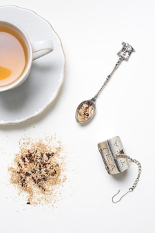 Antique spoon and tea strainer with herbs and tea cup on white background