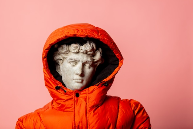 Antique statue dressed in down jacket on pink wall