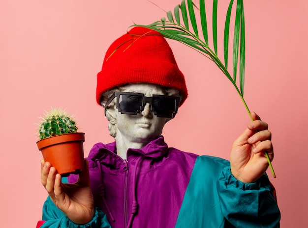 Antique statue dressed in sport suit of the nineties holds cactus and palm branch